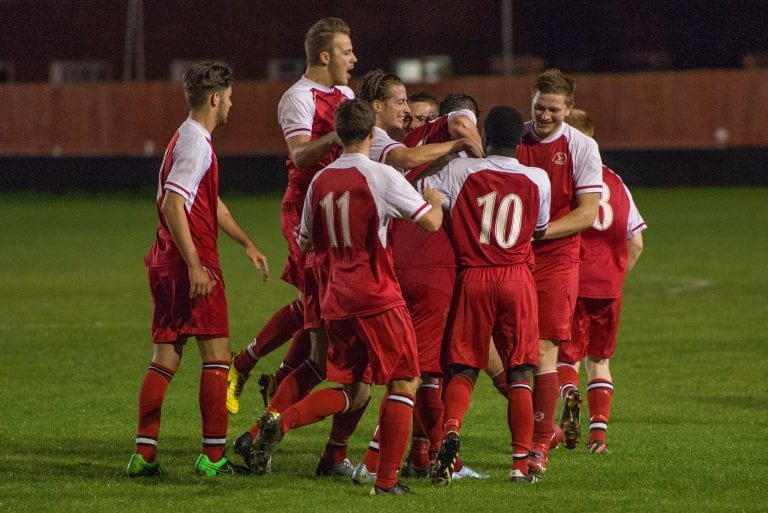 Shane Cooper-Clark is mobbed after scoring for Bracknell Town against Brimscombe & Thrupp in the Emirates FA Cup. Photo: Neil Graham.