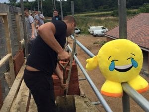 Finchampstead FC's Freddie Barron with the emoji on a building site.