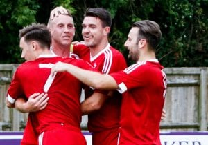 TJ Bohane mobbed by his team mates after scoring for Bracknell Town. Photo: Neil Graham.