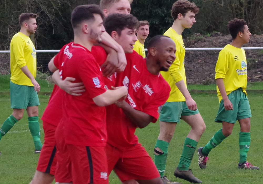 Arron Rowland is mobbed by Binfield FC teammates. Photo: James Green.