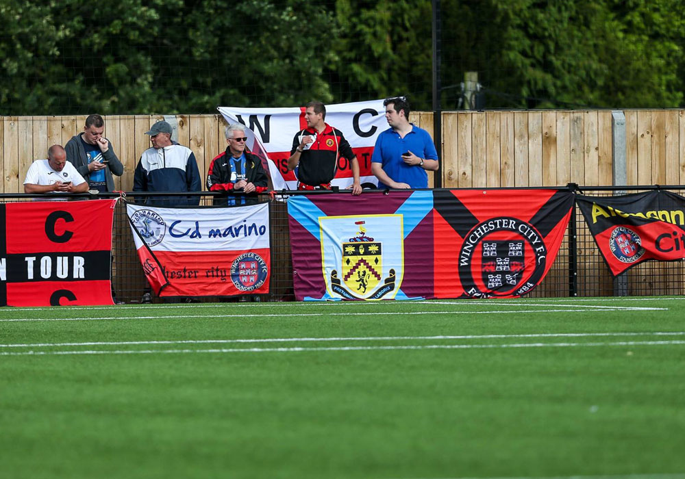 Winchester City supporters and their impressive array of flags. Photo: Neil Graham.