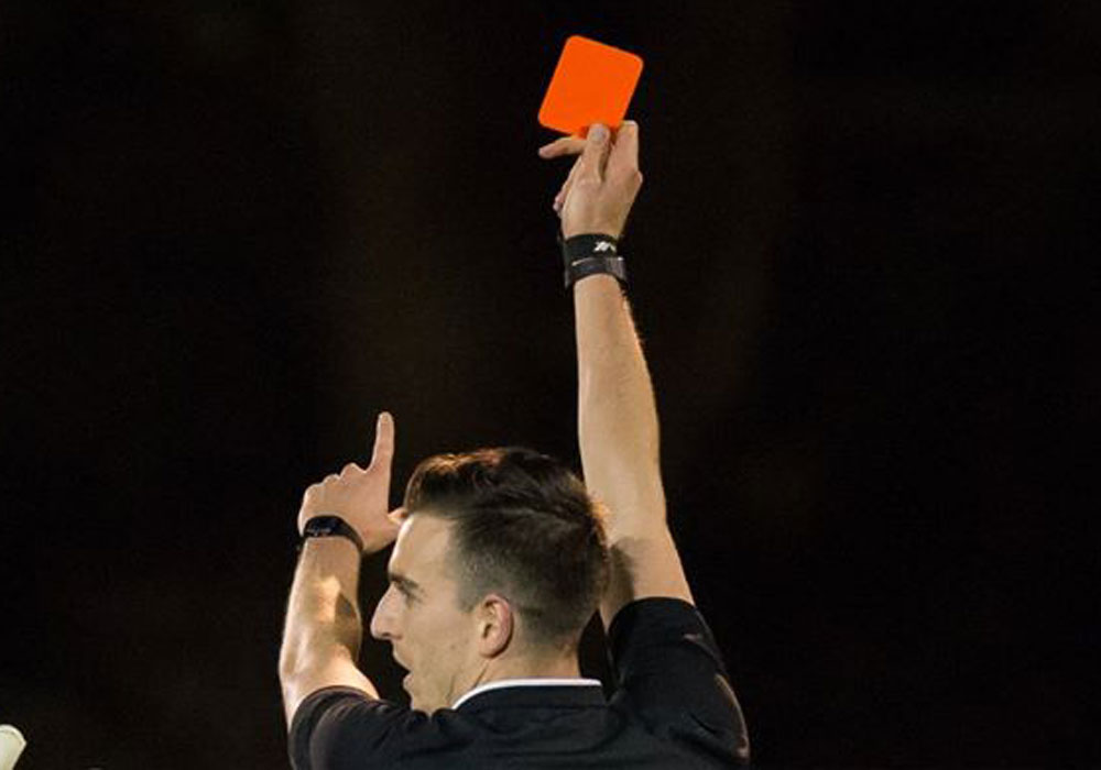 A referee brandishes a red card. Photo: Neil Graham.