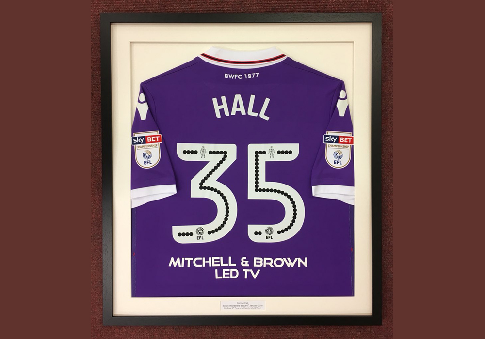 Connor Hall's framed Bolton Wanderers shirt.