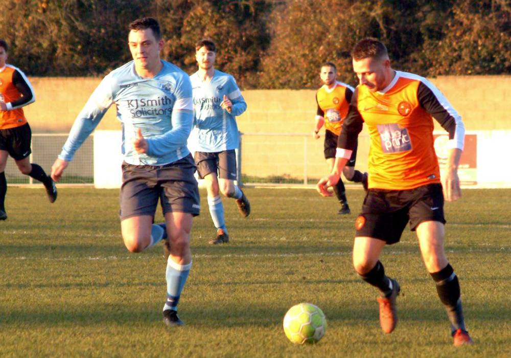Wokingham & Emmbrook's Jake White on the ball with Woodley United's Hamilton Bowler. Photo: Peter Toft.