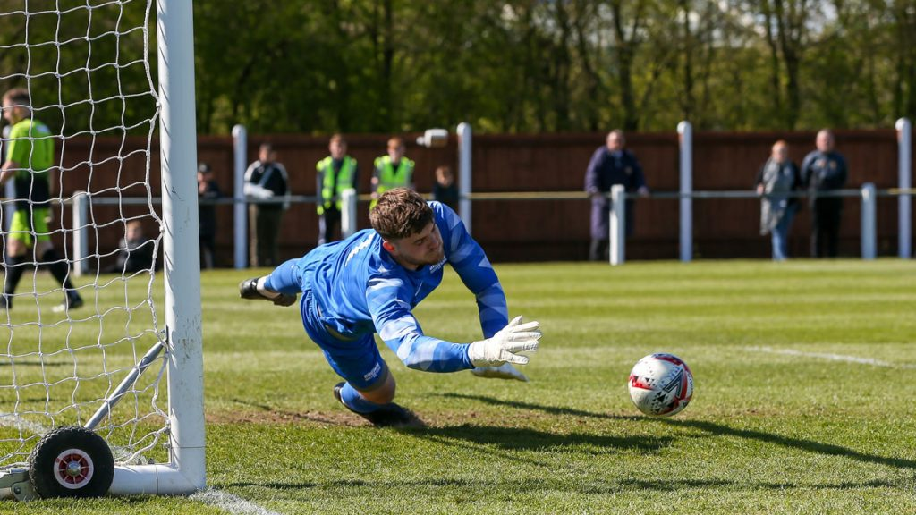 Chris Grace guesses right in the Fakenham Town v Binfield penalty shootout. Photo: Neil Graham / ngsportsphotography.com