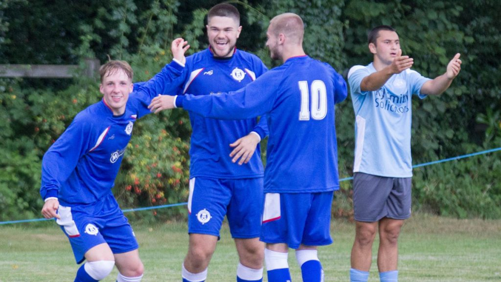 Burghfield's James McClellan is congratulated by Teo Atik and Ollie Brown. Photo: Steve Williams.